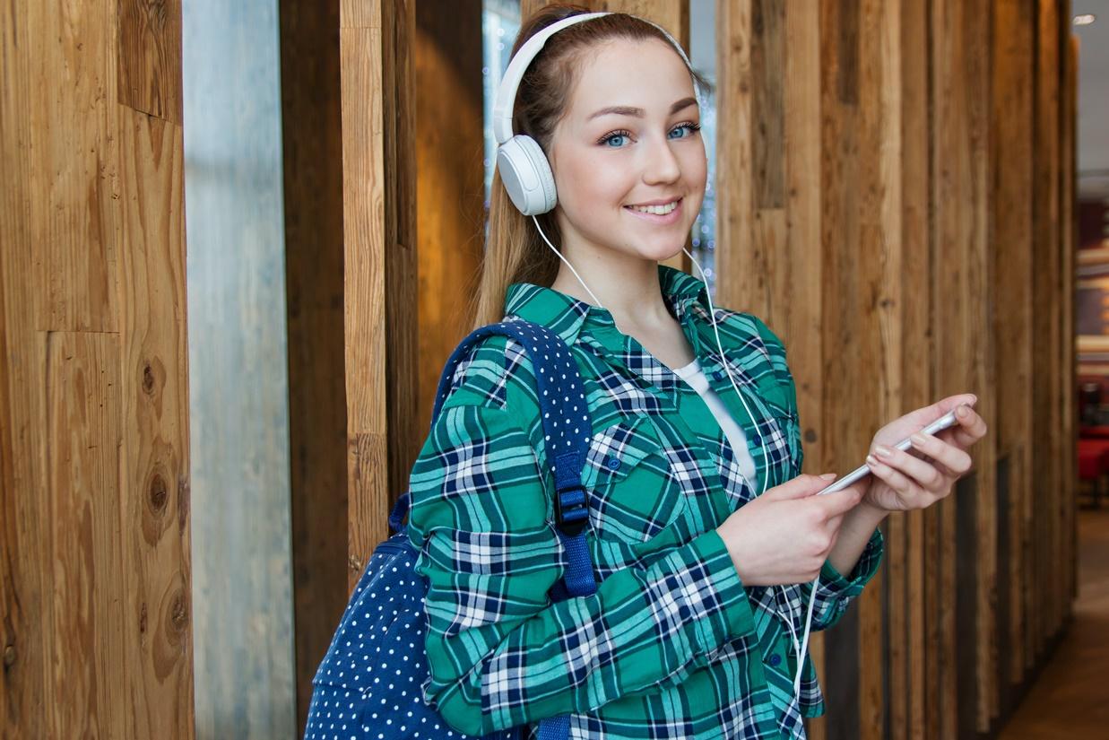 Studentin mit Rucksack, Smartphone und Kopfhörern